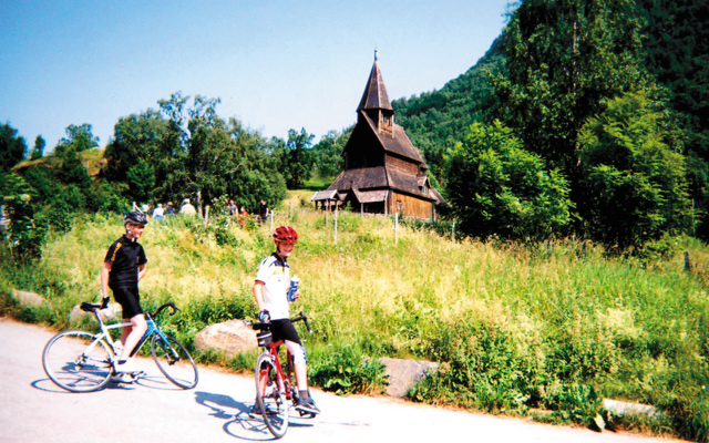 Bikers pass Urnes Stave Church - the oldest still standing. Photo by Carla Waldemar